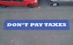 "Carolina Caycedo, DON´T PAY TAXES (Banners series), 2007, banner, nylon, 18' x 3'. Photo Pablo Bernabé, courtesy CGEM. From the exhibition ""CGEM: apuntes sobre la emancipación,"" MUSAC, Spain."
