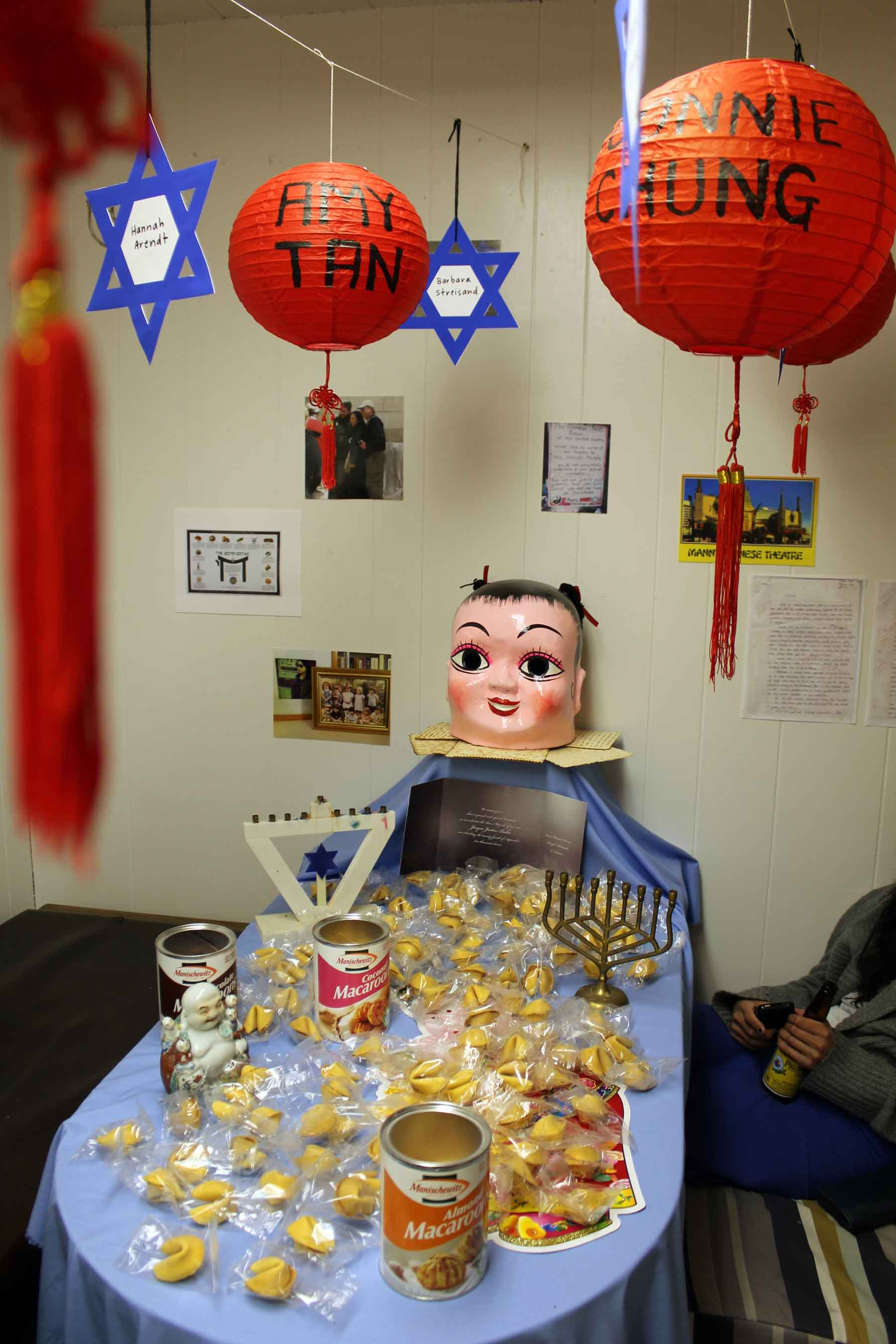 Chan &amp; Mann, Asian-Jew Tablescape, installation of Asian-Jew misfortune cookies, decorations from Chinatown, menorahs, Buddha, incense, inkjet prints of images from the Internet and personal photographs, found Bar Mitzvah announcement, painted paper lanterns, Jewish stars of fame, 2012. Photo: Audrey Chan.