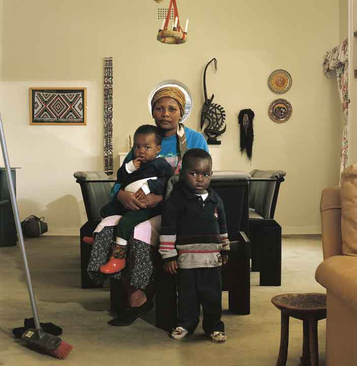 """David Goldblatt, Victoria Cobokana, housekeeper, in her employer's dining room with her son Sifiso and daughter Onica, Johannesburg, 1999. Victoria died of AIDS 13 December 1999, Sifiso died of AIDS 12 January 2000, Onica died of AIDS in May 2000, 1999, photograph (digital print/pigment ink), 33.5"""" × 41.7"""". On long-term loan to Huis Marseille, Amsterdam, NL."""
