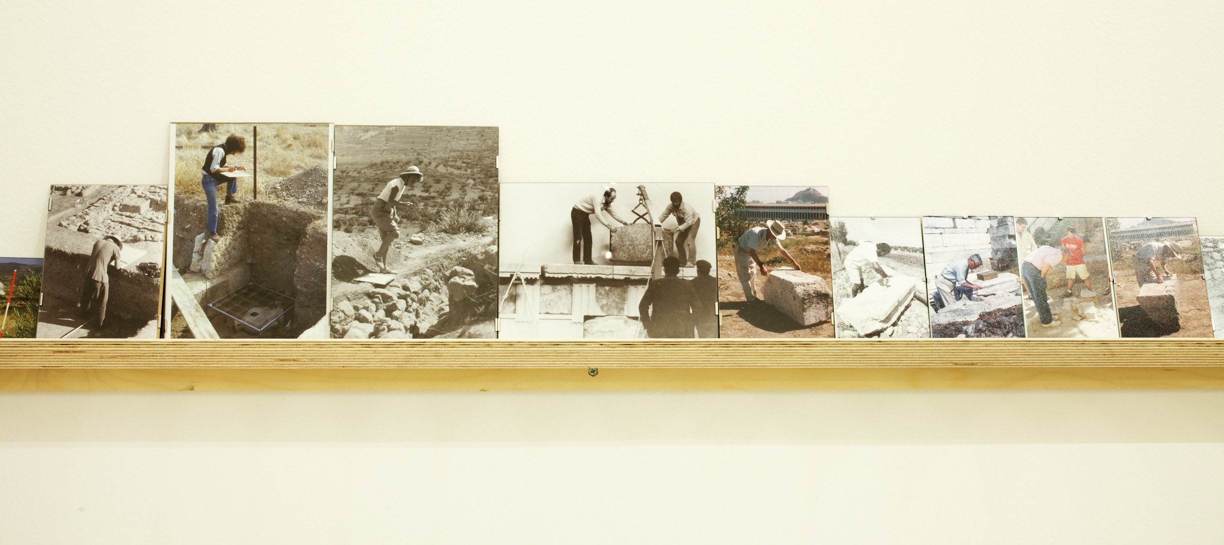 Vangelis Vlahos, Foreign archaeologists from standing to bending position (detail), 2012, 53 framed photos (variable dimensions) on a wall mounted shelf, 27'. Photo: Vivianna Athanassopoulou.
