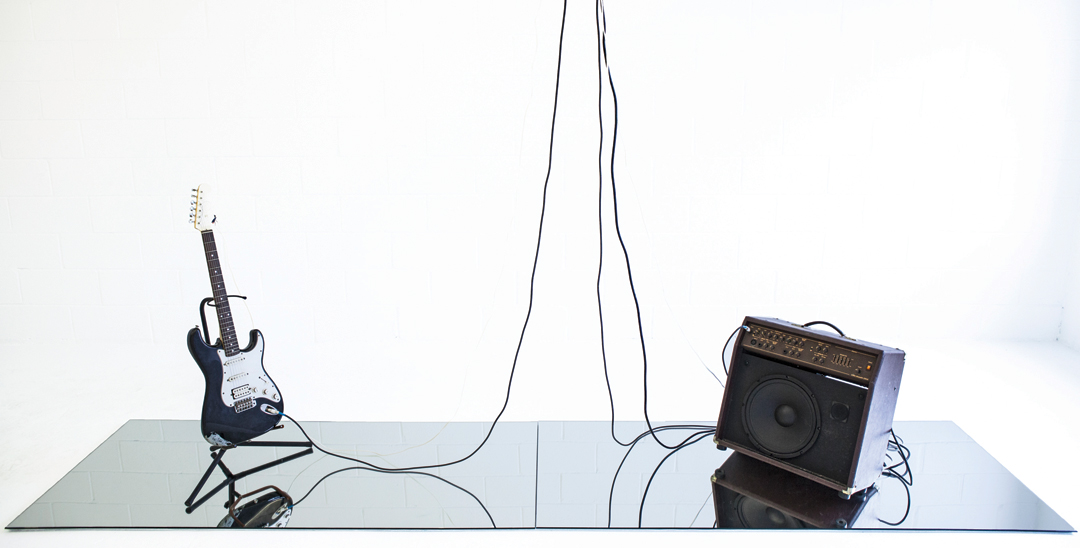 "Richard Garet, Synchronous; the resonance of his voice, 2013, sound installation, electric guitar, guitar amplifier, sound exciter, audio file, 42"" x 30"" x 140,"" continuous running. Courtesy of the artist and Julian Navarro Projects, New York."