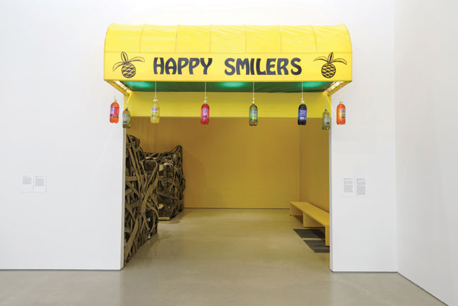 Nari Ward, Happy Smilers: Duty Free Shopping, 1996, awning, plastic soda bottles, fire hose, fire escape, salt, household elements, audio recording, speakers, and aloe vera plant, dimensions variable. Installation view at Pérez Art Museum Miami, 2015  Photo: STUDIO LHOOQ.